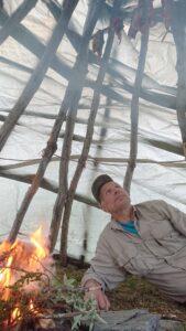 Bilden visar Anders Skum vid en eld.